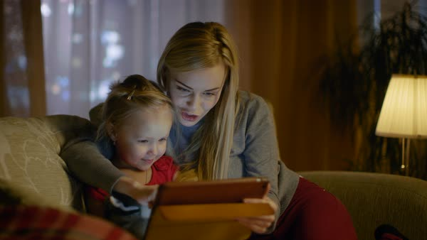 Beautiful mother and her little daughter are sitting on a sofa in the living room, they use tablet computer. It's evening, room is cozy and warm. Royalty-free stock video