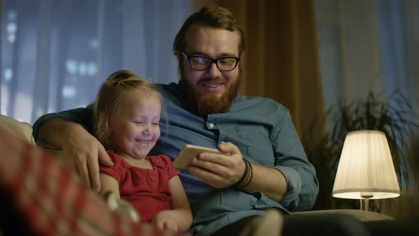 In the evening father and little daughter sitting on a sofa in the living room watch funny videos on smartphone. Royalty-free stock video