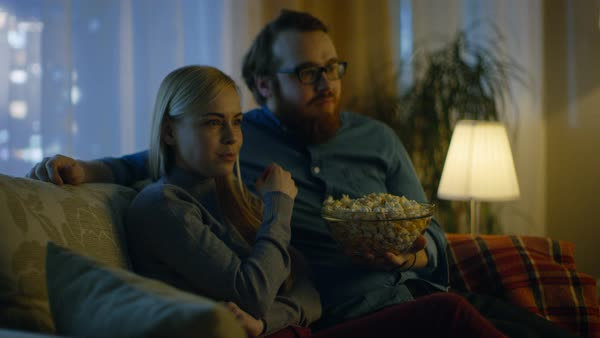 Couple watching tv. They sit on a sofa in their cozy living room and eat popcorn. It's evening. Royalty-free stock video