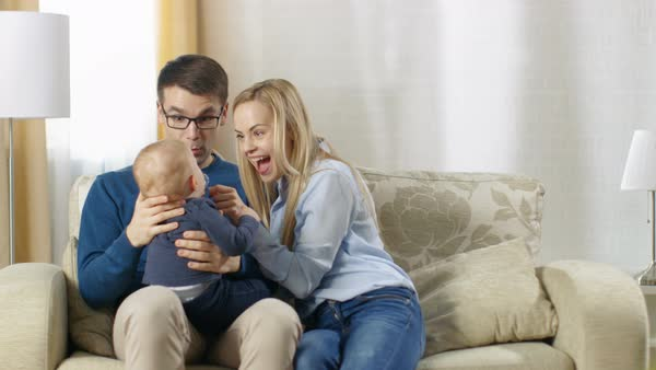 In the living room happy family sitting on a couch. Baby sits on father's lap's both father and mother lovingly cuddle it. Royalty-free stock video