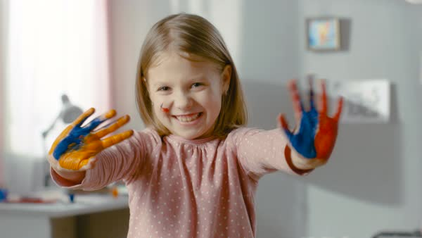 Cute smiling girl shows her hands covered in colourful paint. Royalty-free stock video