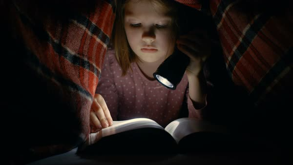 Smart little girl reads interesting book with a flashlight under blanket. Royalty-free stock video