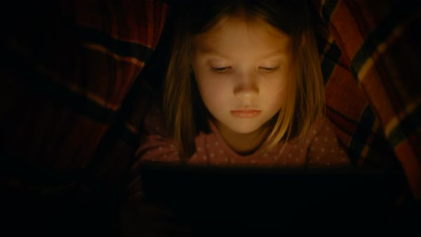 Curious little girl uses tablet computer under cover, at night. Screen illuminates her face. Royalty-free stock video