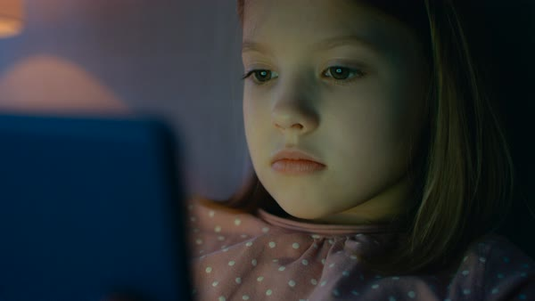 Cute young girl lies in her bed at night and uses tablet computer that illuminates her face. Royalty-free stock video