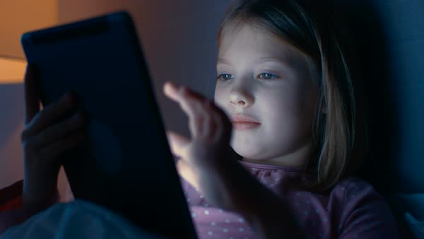 Cute little girl at night in her bed interacts with tablet computer. Royalty-free stock video