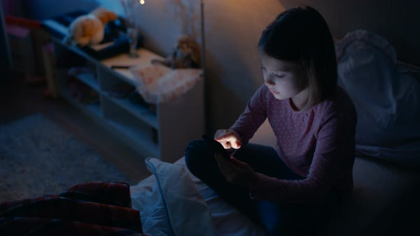 Cute little girl in her room at night. She's sitting on her bed while using smartphone. Her bed light is on. Royalty-free stock video