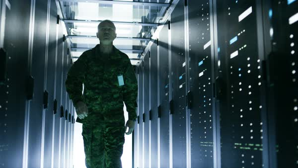 Military man walks through data center with working rack servers. He salutes other soldier in the corridor. Royalty-free stock video