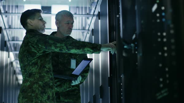In data center two military men work with open server rack cabinet. One holds military edition laptop. Royalty-free stock video