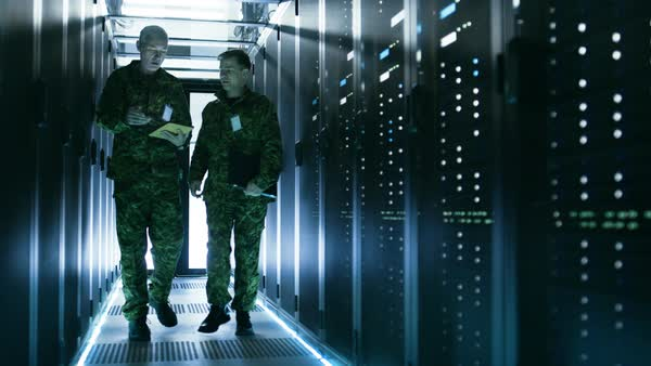 Two military men walking in data center corridor. One uses tablet computer, they have discussion. Rows of working data servers by their sides. Royalty-free stock video