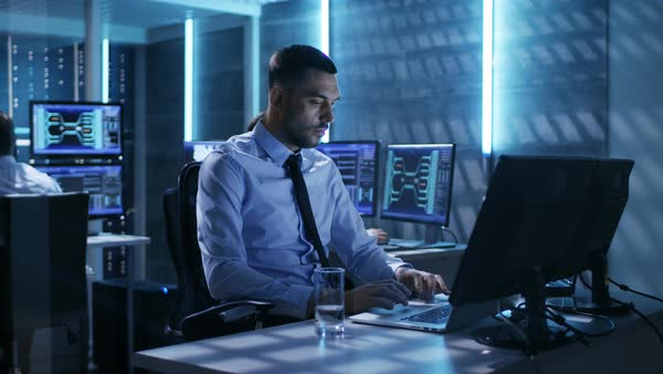 Close-up of technical engineer working on his computer with multiple displays in monitoring room Royalty-free stock video