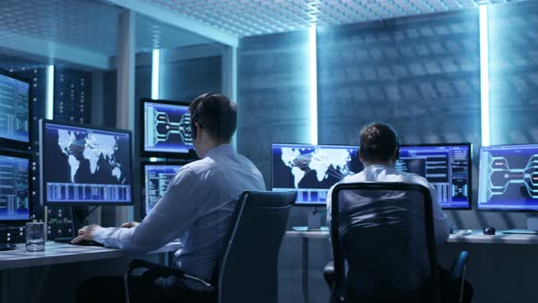 Panorama shot of system control room with three technical controllers working at their workstations with multiple displays Royalty-free stock video