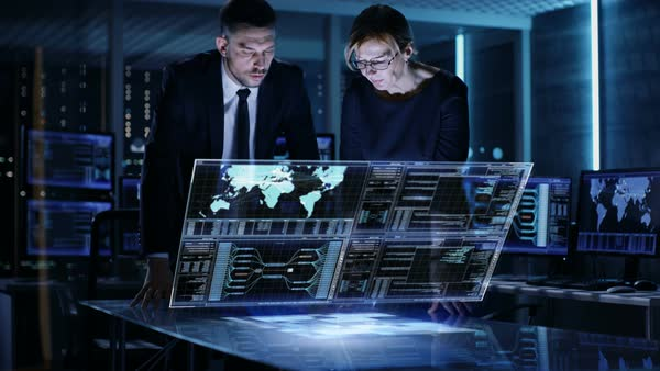 Male and female government agents use touchscreen interactive 3d panel in big monitoring room full of computers with animated screens Royalty-free stock video