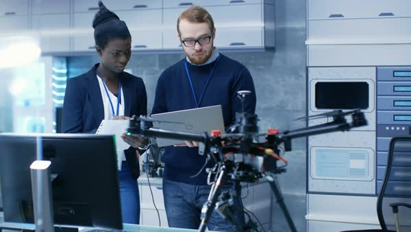 Caucasian male and black female engineers working on a drone project with help of laptop and taking notes Royalty-free stock video