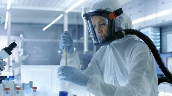 Medical virology research scientist works in a hazmat suit with mask, she takes out test tubes from refrigerator box Royalty-free stock video