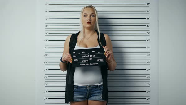 In a police station arrested woman steps in and gets side, front-view mug shot. She wears saucy clothes, has heavy makeup and holds placard. Height chart in the background.  Royalty-free stock video