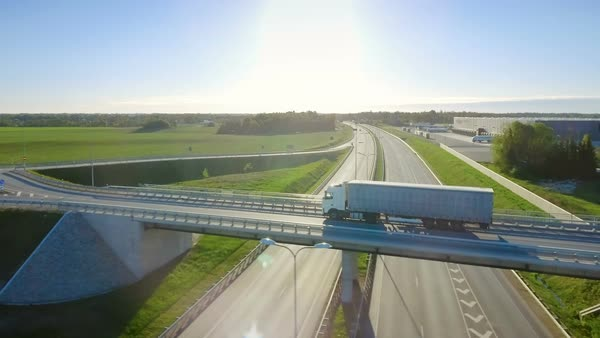 Aerial view of white semi truck with cargo trailer passing highway overpass/ bridge Royalty-free stock video