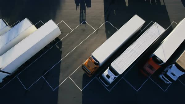 Moving aerial top view of parked semi trucks with cargo/ refrigerator trailers standing on their dedicated parking places Royalty-free stock video