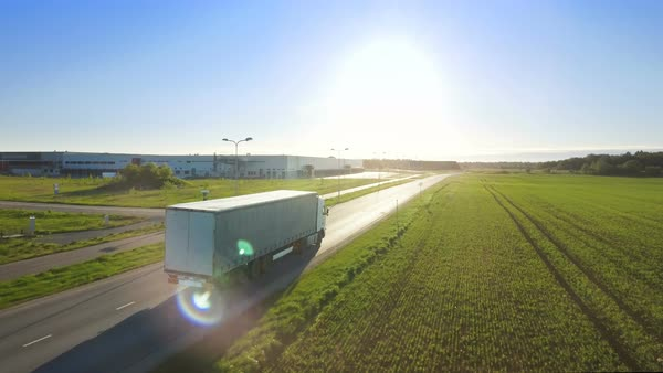 Aerial view of white truck with cargo semi trailer attached drives on the highway Royalty-free stock video