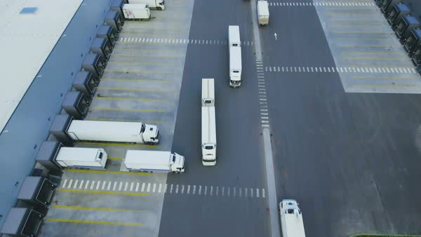 Aerial shot of truck with attached semi trailer leaving industrial warehouse/ storage building/ loading area where many trucks are load/ unload merchandise Royalty-free stock video