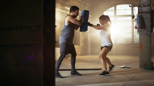 Athletic Woman Hits Punching Bag that Her Partner/ Trainer Holds. Royalty-free stock video