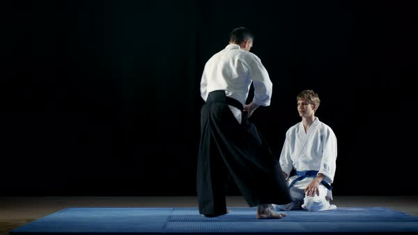 Martial Arts Master Shows Beautiful Aikido Fighting Techniques to His Student Who Looks at Him with Deepest Respect. Shot Isolated on the Black Background.  Royalty-free stock video