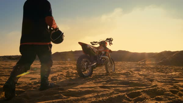 Low angle shot of the professional motocross driver putting on his helmet and getting ready to ride his FMX dirt bike on the quarry sand terrain Royalty-free stock video