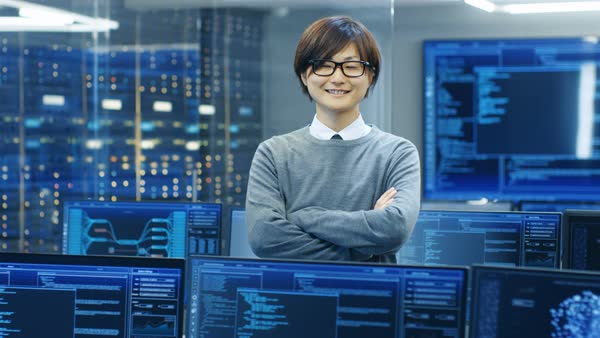 In the System Control Room IT Technician Crosses Arms and Smiles. He's Surrounded by Multiple Displays Showing Graphics.  Royalty-free stock video