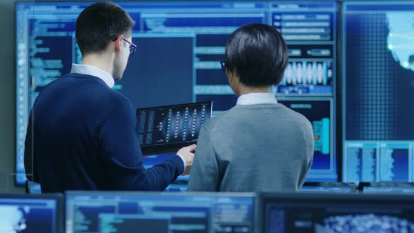 In the System Control Room IT Specialist and Project Engineer Have Discussion, they're surrounded by Multiple Monitors with Graphics. They Work in a Data Center on Data Mining, AI and Neural Networking.  Royalty-free stock video