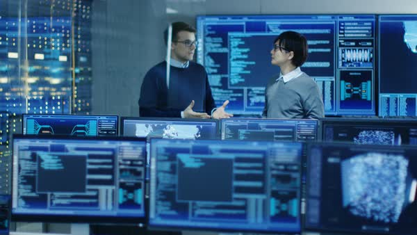 In the Data Center System Control Room Monitors Show Work Done on Neural Networking, AI integration and Data Mining. In the Background Two Specialists Talking.  Royalty-free stock video