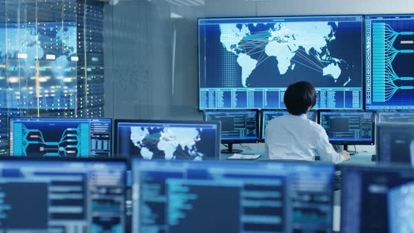 In the System Control Room Operator Sits at His Workstation with Multiple Displays Showing Graphics and Logistics Information.  Royalty-free stock video