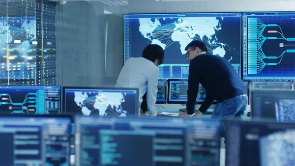 In the System Control Room Project Manage and IT Engineer Have Discussion, they're surrounded by Multiple Monitors with Graphics. Big Monitor Shows Interactive Logistics Map.  Royalty-free stock video