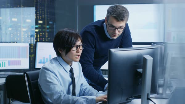 In the Data Mining Center Chief Statistician Consults His Young Assistant sits at His Workstation Surrounded with Monitors Displaying Data and Graphs.  Royalty-free stock video