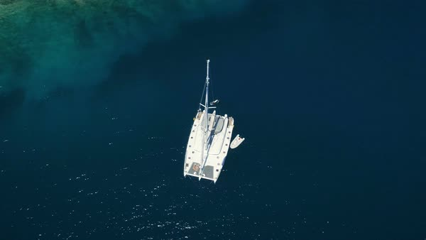 Aerial Top Down Shot of a Big White Sailing Yacht Anchored in a Bay with Man Standup Paddleboarding Near it. Ocean is Dark Blue, with Azure Coral Reef Visible. Royalty-free stock video