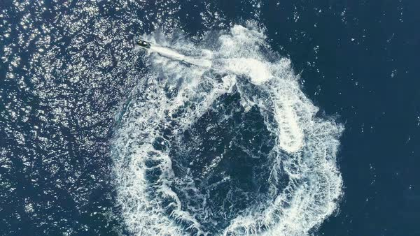 Aerial Top Down View Shot of a Person Jet Skiing in Circles. Beautiful Blue Oceanic Waters and Sun is Shining. Royalty-free stock video