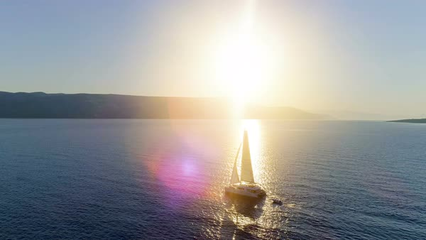 Aerial Long Shot of a Sailing Catamaran Yacht with Raised Sails Traveling Through Open Seas. Sun Shines with Coastal Hills Visible. Royalty-free stock video
