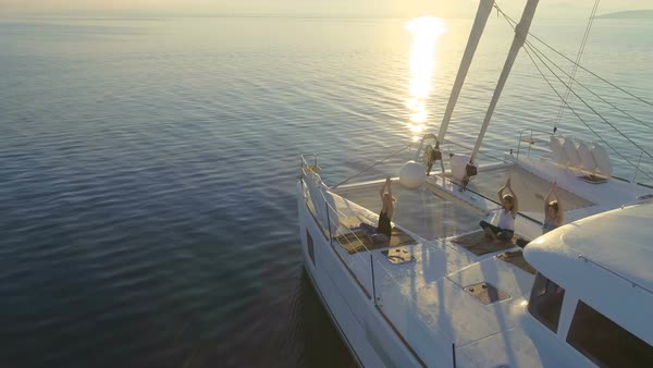 Aerial Side View Shot of Three Beautiful Fit Women Doing Morning Yoga on a White Sailing Catamaran Boat. Peaceful Sea with Rising Sun and Calm Sea. Royalty-free stock video