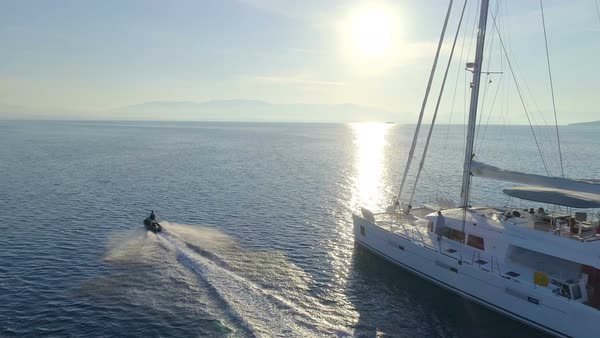 Aerial View of the White Sailing Catamaran Yacht and Jet Ski Driving by. Beautiful Weather with Calm Mirror Like Sea and Sun Shining. Royalty-free stock video