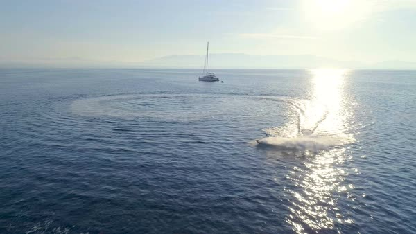 Aerial View of the White Sailing Catamaran Yacht and Jet Ski Driving in Circles Near by. Beautiful Weather with Calm Mirror Like Sea and Sun Shining. Royalty-free stock video