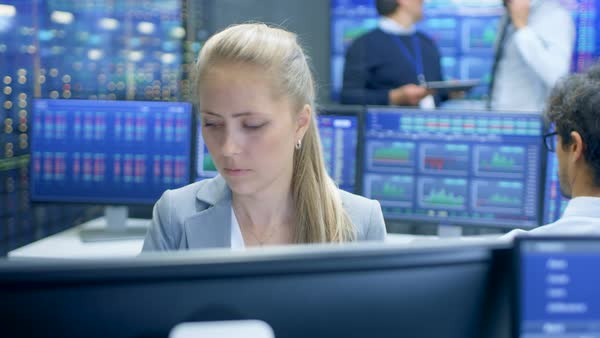 Experienced stock exchange trader making sales and buys at her workstation. Multi-ethnic team at stock exchange office is busy selling and buying stocks on the market. Displays show relevant data numbers.  Royalty-free stock video