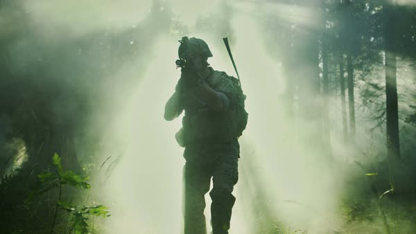 Silhouette of the fully equipped soldier moving through smokey forest with rifle ready to shoot. Reconnaissance military operation. Squad moving behind him.  Royalty-free stock video