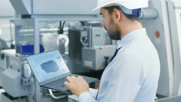 Chief engineer in the hard hat holds laptop with 3D component model on it's screen Royalty-free stock video