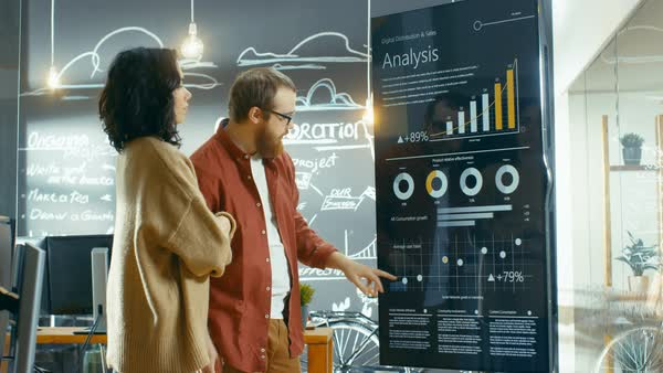 Female developer and male statistician use interactive whiteboard presentation touchscreen to look at charts, graphs and growth statistics. They work in the stylish creative office.  Royalty-free stock video