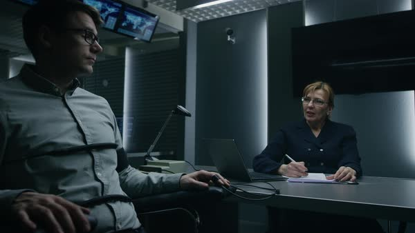 Young handsome suspect during interrogation undergoes lie detector