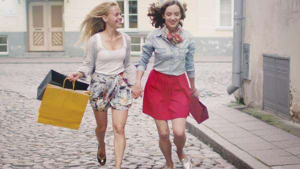 Two happy girls is running with bags on streets of European town Royalty-free stock video