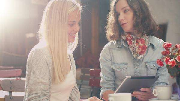 Two girls are talking and using tablet in outdoor coffee shop Royalty-free stock video