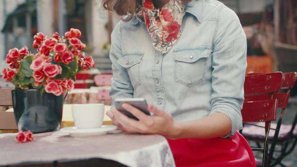 Young girl is using mobile phone in outdoor coffee shop Royalty-free stock video
