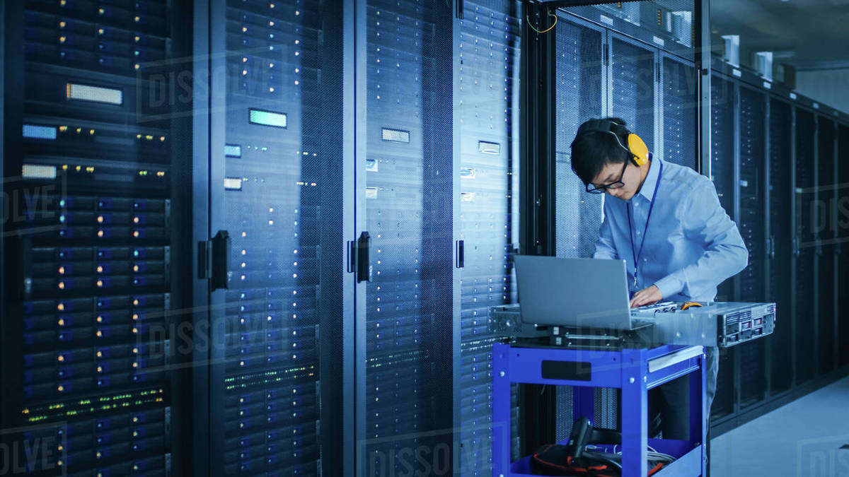 In the Modern Data Center: IT Technician Wearing Protective Headphones  Working with Server Racks, on a Pushcart Installing New Hardware  Engineer