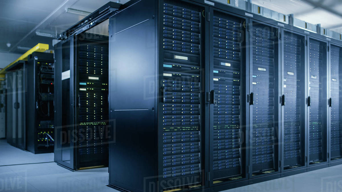 Shot of Data Center With Multiple Rows of Fully Operational Server Racks. Modern Telecommunications, Cloud Computing, Artificial Intelligence, Database, Super Computer Technology Concept. - Stock Photo - Dissolve