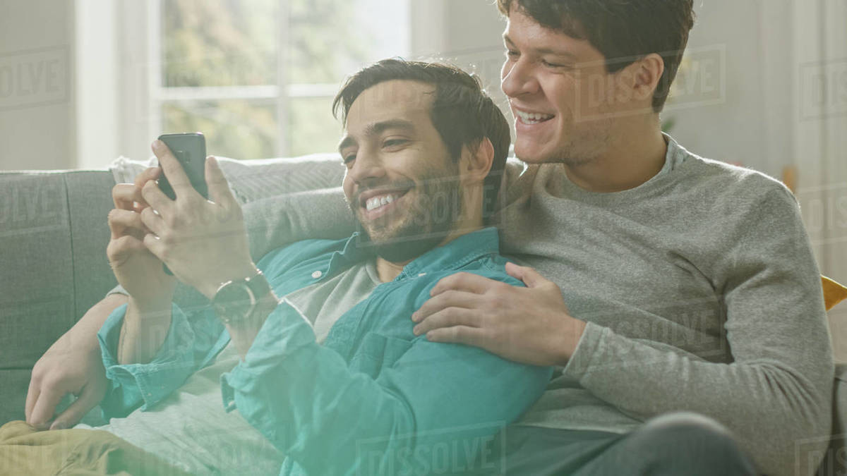 Cute male gay couple spend time at home. They are lying down on a sofa and use a smartphone. They browse online. Partner's hand is around his lover. They smile and laugh. Room has modern interior.  Royalty-free stock photo