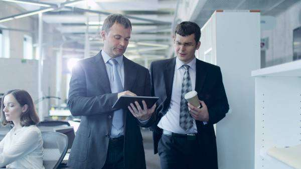Two businessmen are walking through office. office worker holding tablet pc. Royalty-free stock video